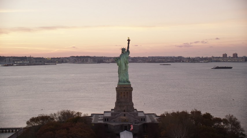 6K stock footage aerial video of circling behind the Statue of Liberty at sunrise, New York Aerial Stock Footage | AX118_054