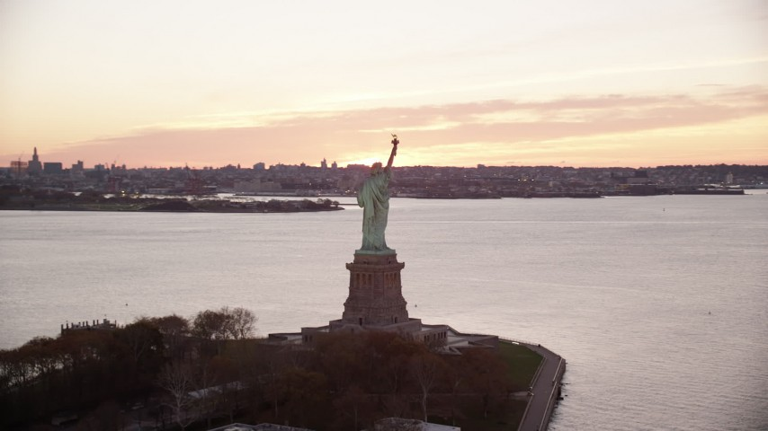 6K stock footage aerial video of orbiting the Statue of Liberty at sunrise, Brooklyn in background, New York Aerial Stock Footage | AX118_055