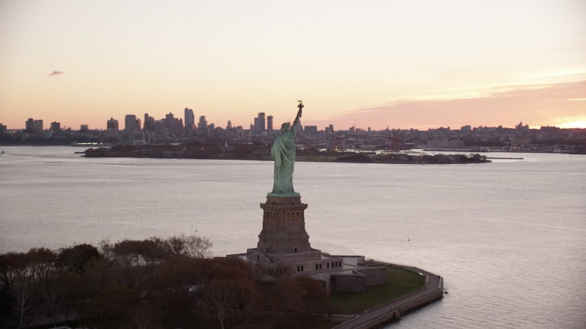 6K stock footage aerial video of flying around the side of the Statue of Liberty at sunrise, New York Aerial Stock Footage   AX118_056