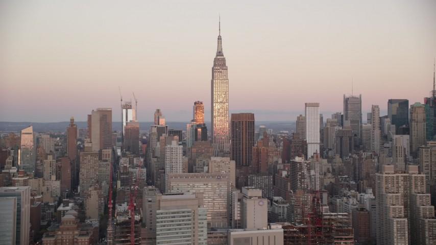 6K stock footage aerial video of the famous Empire State Building at sunrise in Midtown Manhattan, New York City Aerial Stock Footage | AX118_063