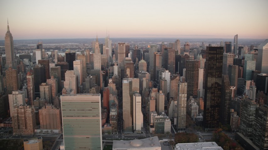 6K stock footage aerial video of the UN, Chrysler Building and skyscrapers at sunrise in Midtown, New York City Aerial Stock Footage | AX118_068