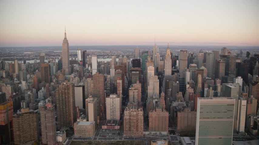 6K stock footage aerial video flyby the UN, Chrysler and Empire State Building at sunrise in Midtown, New York City Aerial Stock Footage | AX118_069