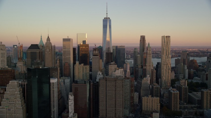 5.5K stock footage aerial video of the top of Freedom Tower and Lower Manhattan skyscrapers at sunrise in New York City Aerial Stock Footage | AX118_075
