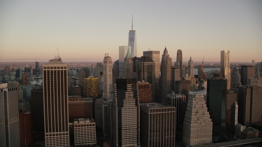 6K stock footage aerial video of flying by Lower Manhattan skyscrapers at sunrise in New York City Aerial Stock Footage | AX118_076