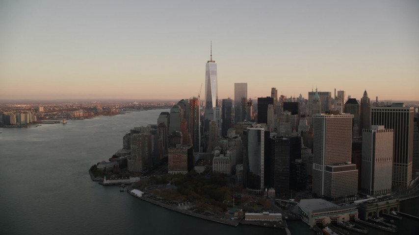 6K stock footage aerial video of a view of Lower Manhattan skyscrapers and Battery Park at sunrise in New York City Aerial Stock Footage | AX118_079
