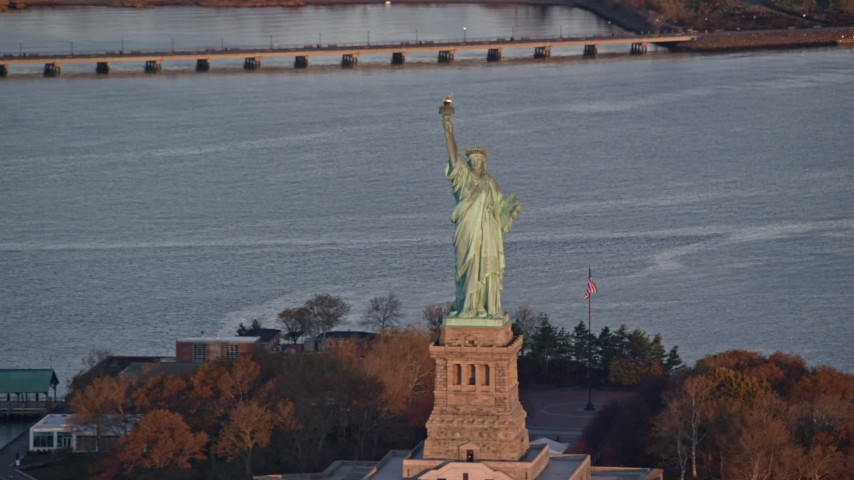 6K stock footage aerial video orbit the iconic Statue of Liberty monument at sunrise, New York Aerial Stock Footage | AX118_082
