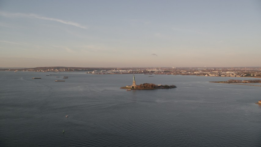 6K stock footage aerial video of a wide view of Statue of Liberty at sunrise in New York Aerial Stock Footage   AX118_102