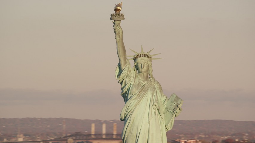 6K stock footage aerial video of orbiting the Statue of Liberty monument at sunrise in New York Aerial Stock Footage | AX118_106