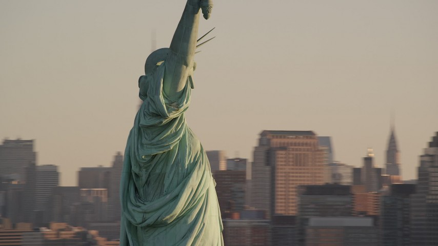 6K stock footage aerial video of a close orbit around the Statue of Liberty at sunrise in New York Aerial Stock Footage   AX118_109