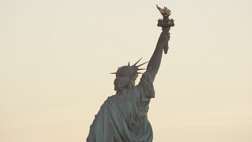 6K aerial video of a close orbit around the back of the Statue of Liberty at sunrise in New York Aerial Stock Footage | AX118_110