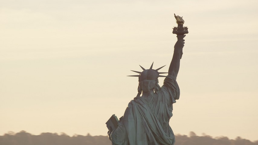 6K stock footage aerial video closely orbiting the Statue of Liberty with the rising sun overhead in New York Aerial Stock Footage | AX118_111