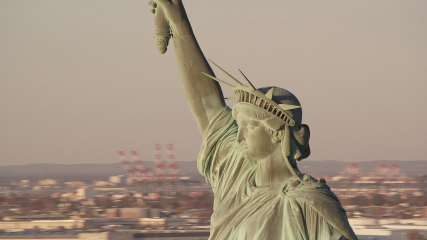 6K stock footage aerial video of orbiting the Statue of Liberty monument at sunrise in New York Aerial Stock Footage AX118_115