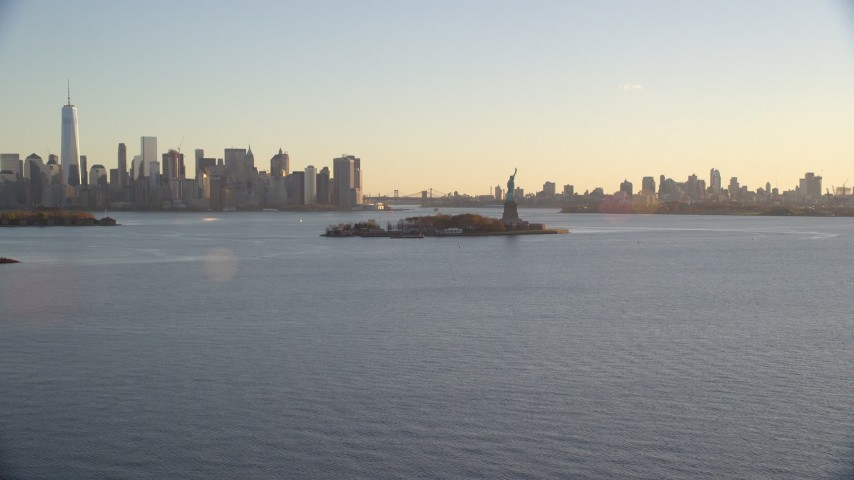 6K stock footage aerial video wide view of Statue of Liberty and Brooklyn and Lower Manhattan skylines at sunrise in New York Aerial Stock Footage AX118_119 | Axiom Images