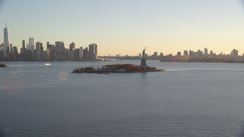 6K stock footage aerial video approach Statue of Liberty and Brooklyn and Lower Manhattan skylines at sunrise in New York Aerial Stock Footage | AX118_120