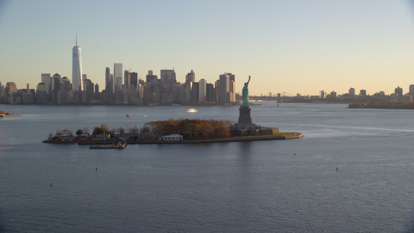 6K stock footage aerial video of Statue of Liberty and Lower Manhattan skyline at sunrise in New York Aerial Stock Footage | AX118_121