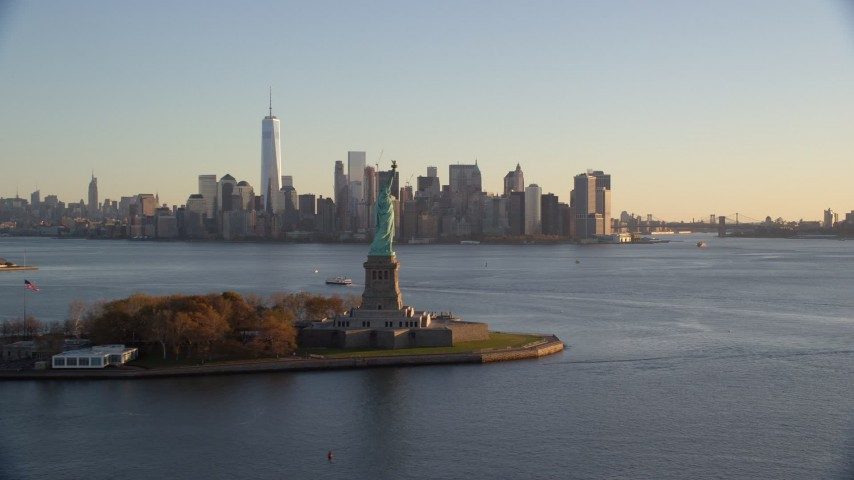 6K stock footage aerial video flyby Statue of Liberty for view of Lower Manhattan skyline at sunrise in New York Aerial Stock Footage AX118_122 | Axiom Images