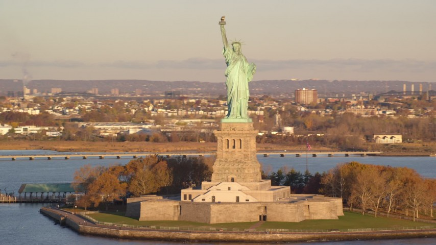 6K stock footage aerial video of orbiting the front of the Statue of Liberty monument at sunrise in New York Aerial Stock Footage | AX118_124