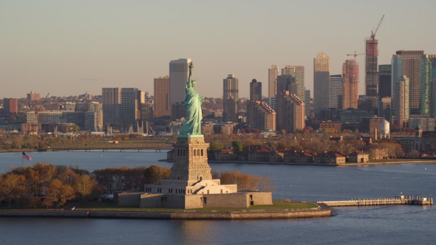 6K stock footage aerial video orbit Statue of Liberty, reveal Jersey City skyline at sunrise in New York Aerial Stock Footage | AX118_126