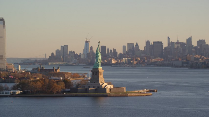 6K stock footage aerial video of Statue of Liberty and Midtown skyline at sunrise in New York Aerial Stock Footage | AX118_128