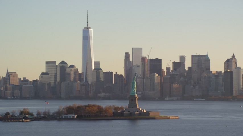 6K stock footage aerial video of Statue of Liberty and Lower Manhattan skyline at sunrise in New York Aerial Stock Footage | AX118_129