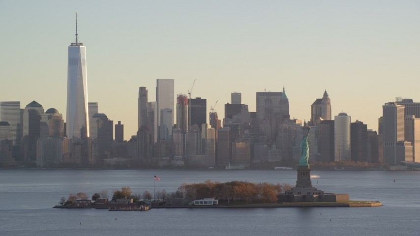 6K stock footage aerial video of a view of Statue of Liberty and Lower Manhattan skyline at sunrise in New York Aerial Stock Footage | AX118_130
