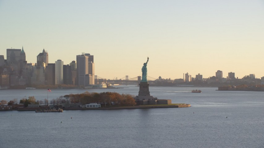 6K stock footage aerial video approach the Statue of Liberty at sunrise in New York Aerial Stock Footage | AX118_131