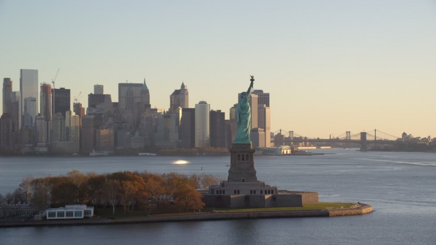 6K stock footage aerial video of flying by Statue of Liberty at sunrise with view of Lower Manhattan, New York Aerial Stock Footage   AX118_132