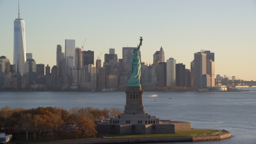6K aerial video flyby Statue of Liberty to focus on Lower Manhattan skyline at sunrise in New York City Aerial Stock Footage | AX118_133