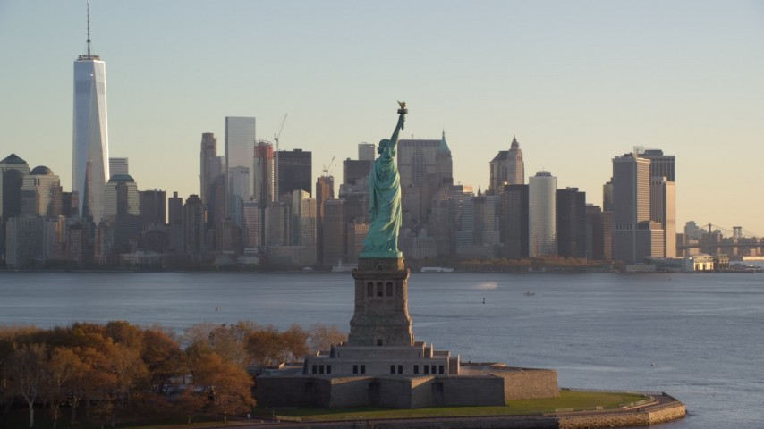 Statue of Liberty and Lower Manhattan Skyline at Sunrise in New York City Aerial Stock Footage | AX118_134