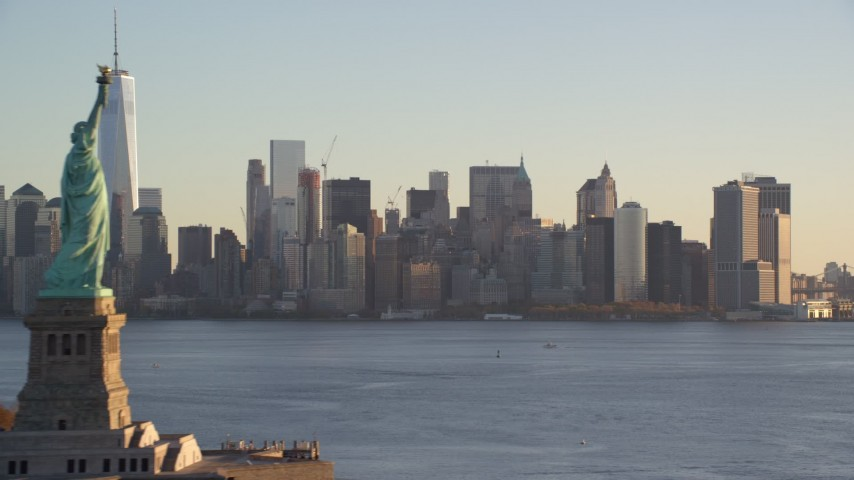 6K stock footage aerial video of passing Statue of Liberty to focus on Lower Manhattan skyline at sunrise in New York City Aerial Stock Footage | AX118_134
