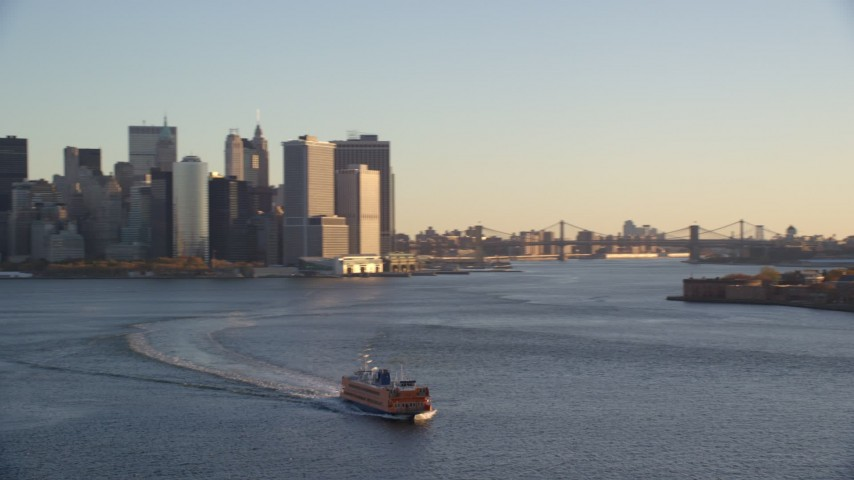 5.5K stock footage aerial video orbit Staten Island Ferry near Lower Manhattan skyline at sunrise in New York City Aerial Stock Footage | AX118_135