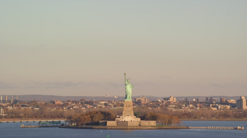 6K aerial video of Statue of Liberty and hazy sky at sunrise in New York Aerial Stock Footage | AX118_136
