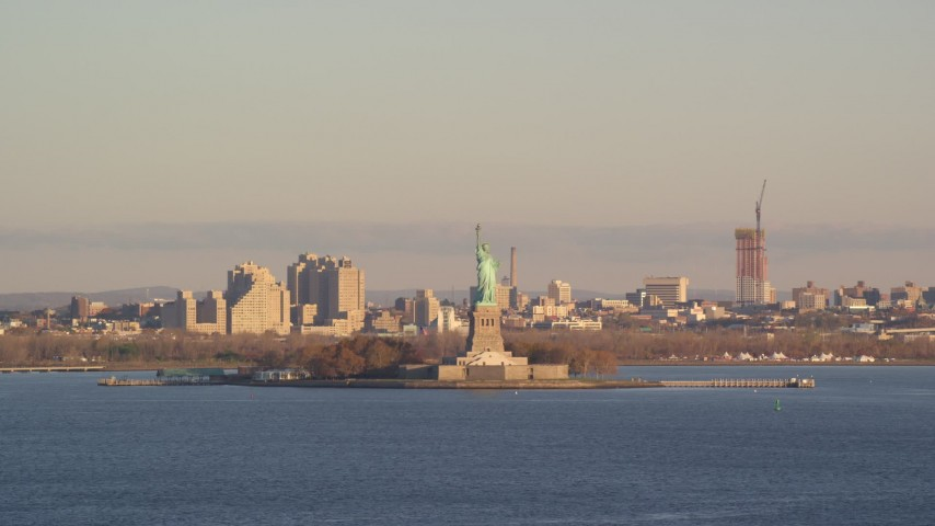 6K stock footage aerial video of flying by Statue of Liberty at sunrise in New York Aerial Stock Footage | AX118_139