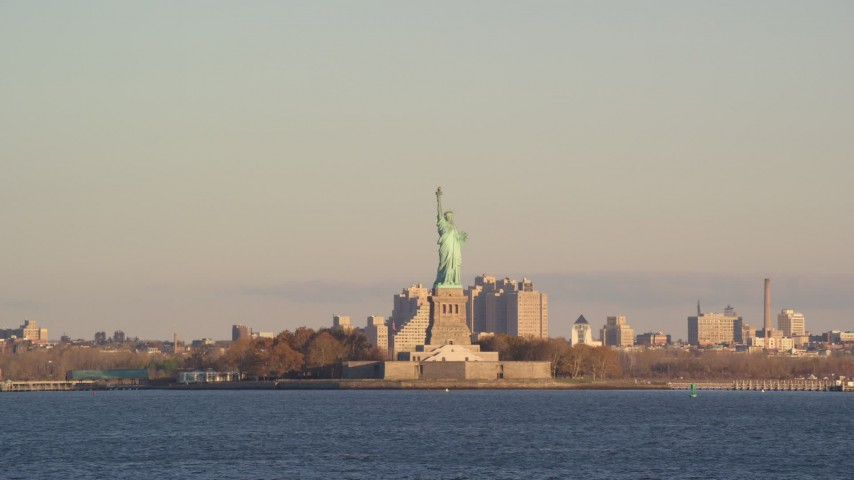 6K stock footage aerial video low altitude view of Statue of Liberty at sunrise in New York Aerial Stock Footage | AX118_140
