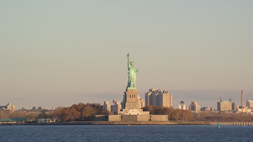6K stock footage aerial video of low altitude approach to Statue of Liberty at sunrise in New York Aerial Stock Footage | AX118_141