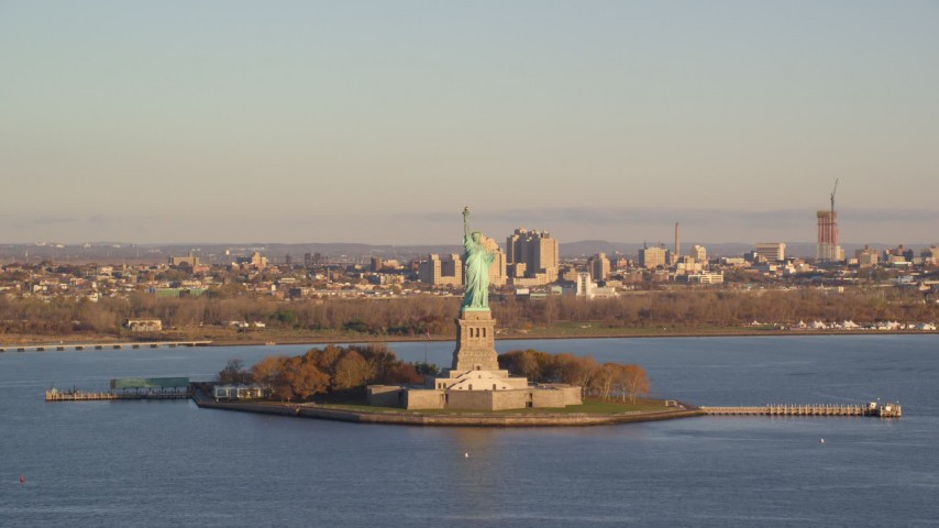 6K stock footage aerial video ascend and approach Statue of Liberty at sunrise in New York Aerial Stock Footage | AX118_143