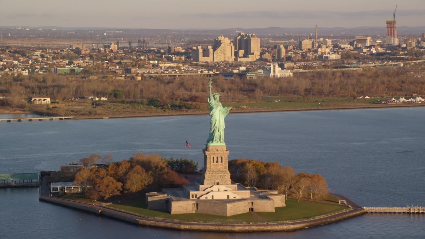 6K stock footage aerial video approach and tilt to the Statue of Liberty at sunrise in New York Aerial Stock Footage | AX118_144