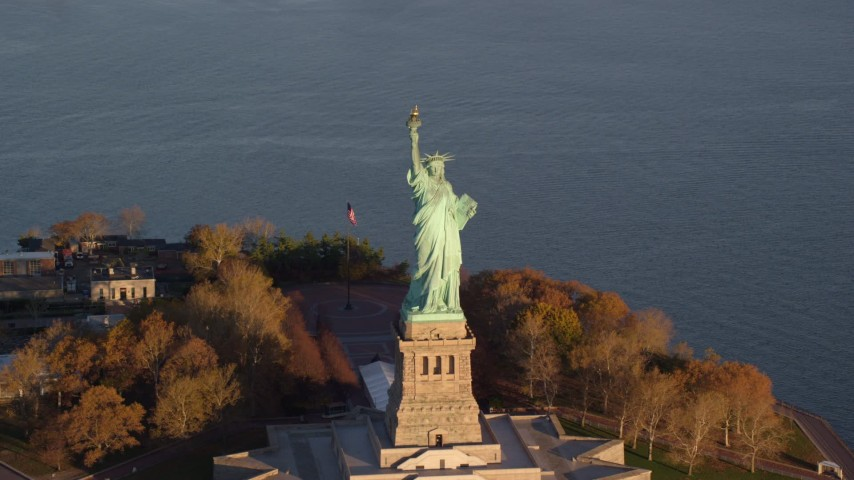 6K stock footage aerial video approach and tilt to the Statue of Liberty monument at sunrise in New York Aerial Stock Footage | AX118_145