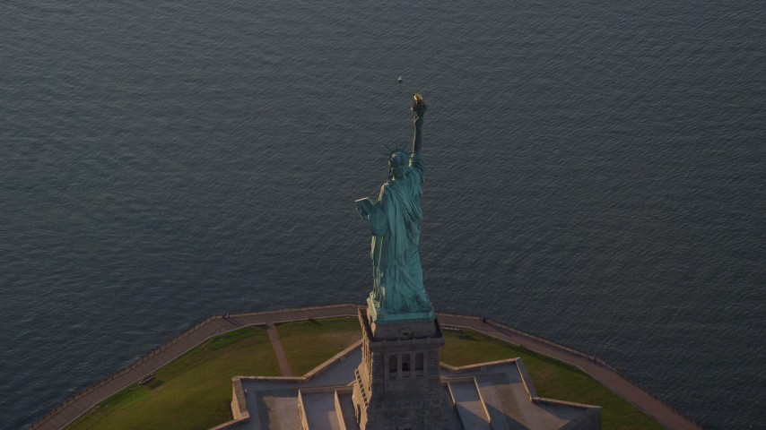 6K stock footage aerial video of flying away from the Statue of Liberty at sunrise in New York Aerial Stock Footage | AX118_148
