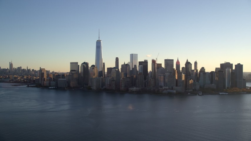 5.5K stock footage aerial video of approaching the Lower Manhattan skyline by the Hudson at sunrise in New York City Aerial Stock Footage | AX118_151