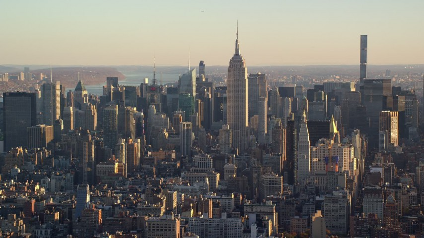6K aerial video of orbiting the iconic Empire State Building and Midtown at sunrise in New York City Aerial Stock Footage | AX118_169