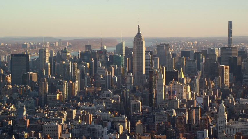 6K stock footage aerial video of the Empire State Building towering over Midtown at sunrise in New York City Aerial Stock Footage | AX118_170