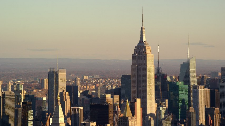 6K stock footage aerial video of the Empire State Building towering over Midtown at sunrise in New York City Aerial Stock Footage | AX118_173