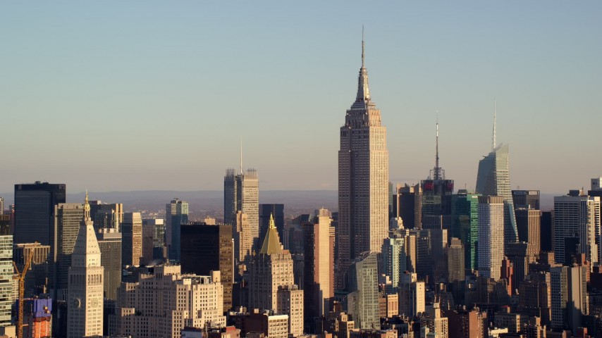 5.5K stock footage aerial video of approaching the Empire State Building towering over Midtown at sunrise in New York City Aerial Stock Footage | AX118_175E