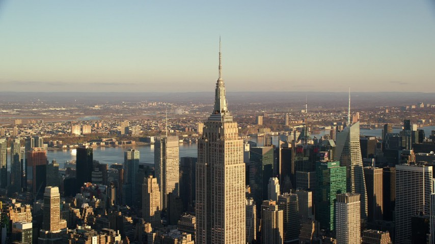 6K stock footage aerial video approach top spire of the Empire State Building at sunrise in New York City Aerial Stock Footage | AX118_179