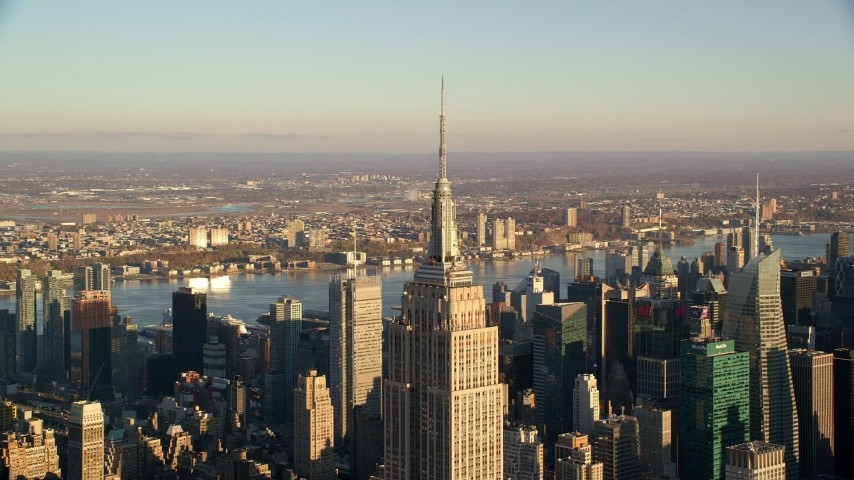 6K stock footage aerial video of approaching the spire atop the Empire State Building at sunrise in New York City Aerial Stock Footage | AX118_180