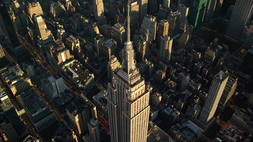 6K stock footage aerial video approaching the spire atop the Empire State Building at sunrise in New York City Aerial Stock Footage | AX118_182