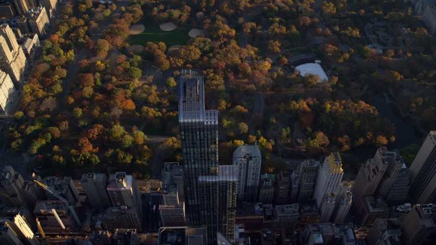 6K stock footage aerial video approach One57 skyscraper and Central Park with Autumn leaves at sunrise in New York City Aerial Stock Footage | AX118_189