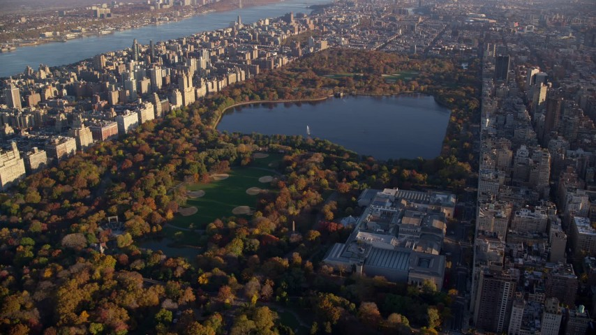 6K stock footage aerial video of Central Park and The Met with Autumn leaves at sunrise in New York City Aerial Stock Footage | AX118_192