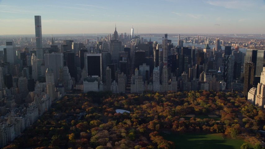 5.5K stock footage aerial video of Central Park with Autumn leaves and Midtown at sunrise in New York City Aerial Stock Footage   AX118_194E